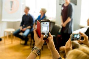 telefon trzymany w ręce, z tyłu widoczna grupa ludzi