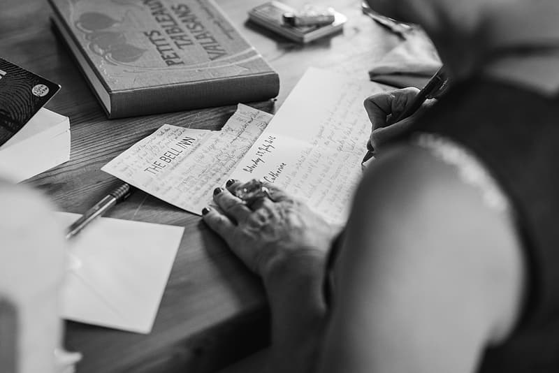 person-writing-letter-grayscale-photo